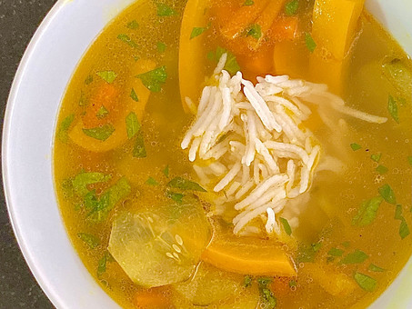 Golden broth with peas, cucumbers, and yellow peppers