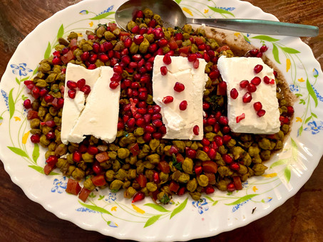 Braised green chickpeas with pomegranate and feta