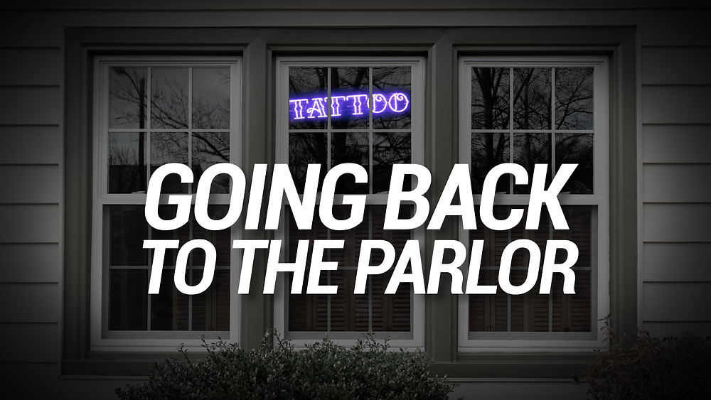 """Three tall, narrow windows with various panes in wooden, white-painted frames, and a neon """"tattoo"""" sign inside, implying that it's open"""