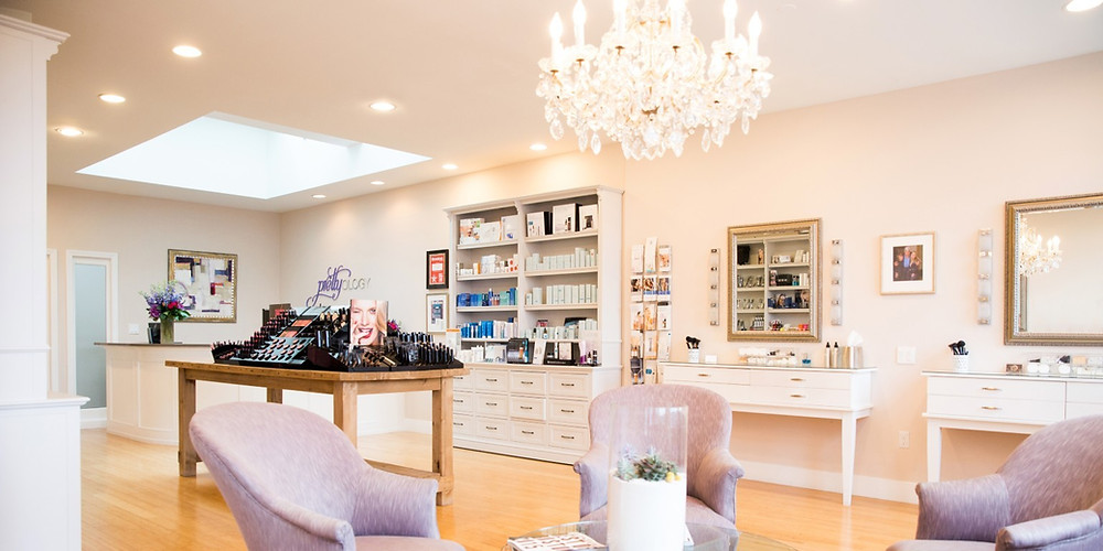 A beautifully-decorated salon in light hues, a chandelier, plush, small chairs in a waiting area with a coffee table
