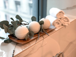 Our Lavender and Eucalyptus CBD Bath Bombs chilling on a window sill with Pittsburgh in the backgrou