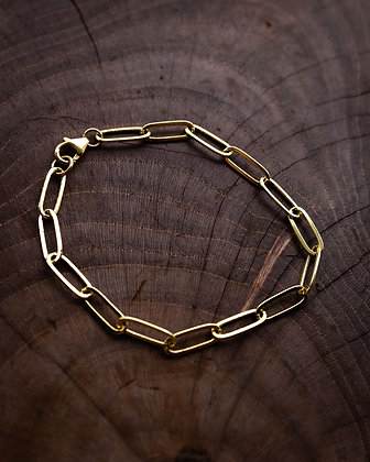 Gold paperclip chain bracelet on wood