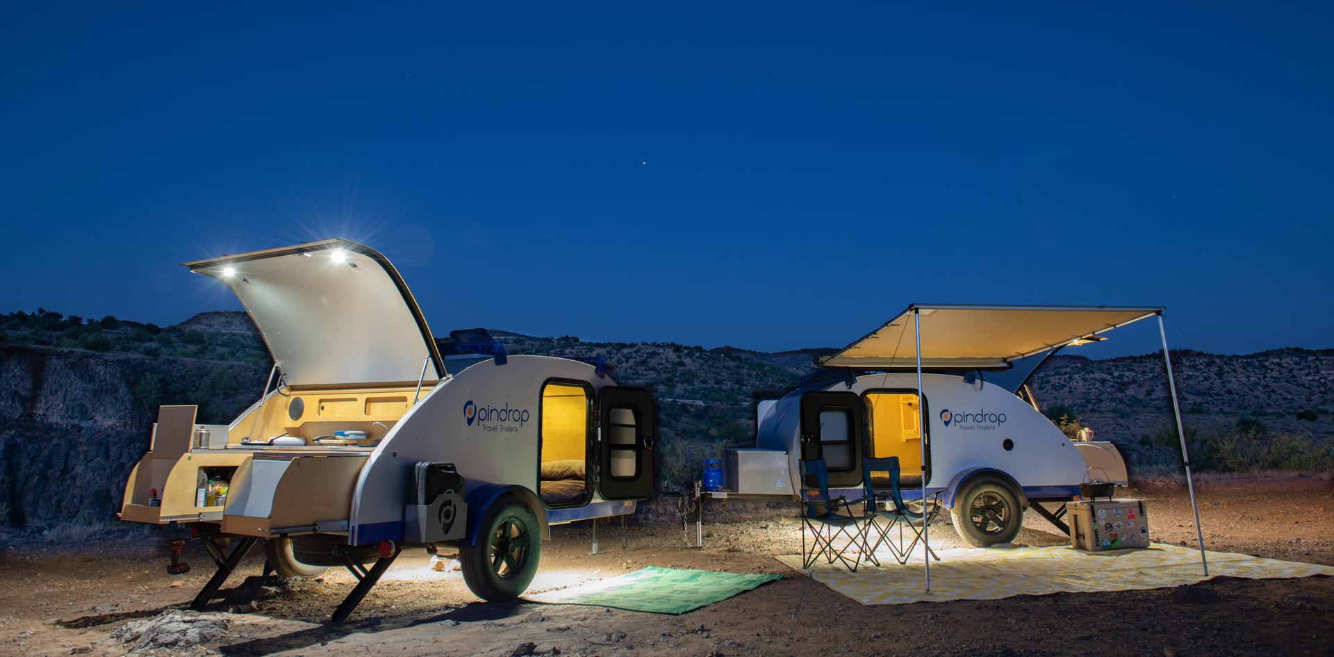 Pin Drop Travel Trailers lit up at night