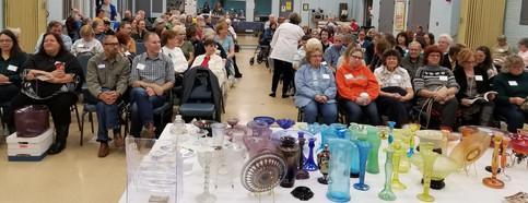 Michigan Depression Glass Society members watch a program on iridescent stretch glass