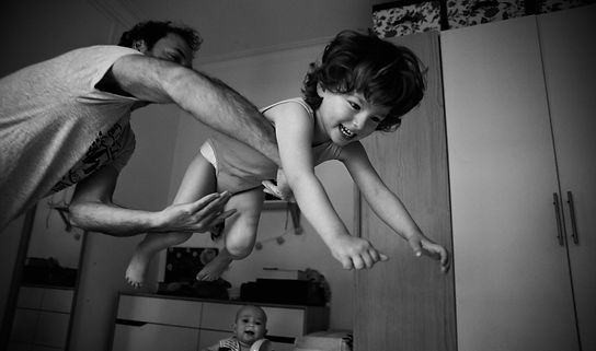 boy playing with dad in bedroom