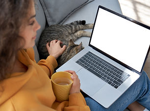Young hispanic latin teen girl student relax sit on sofa with cat holding laptop looking a