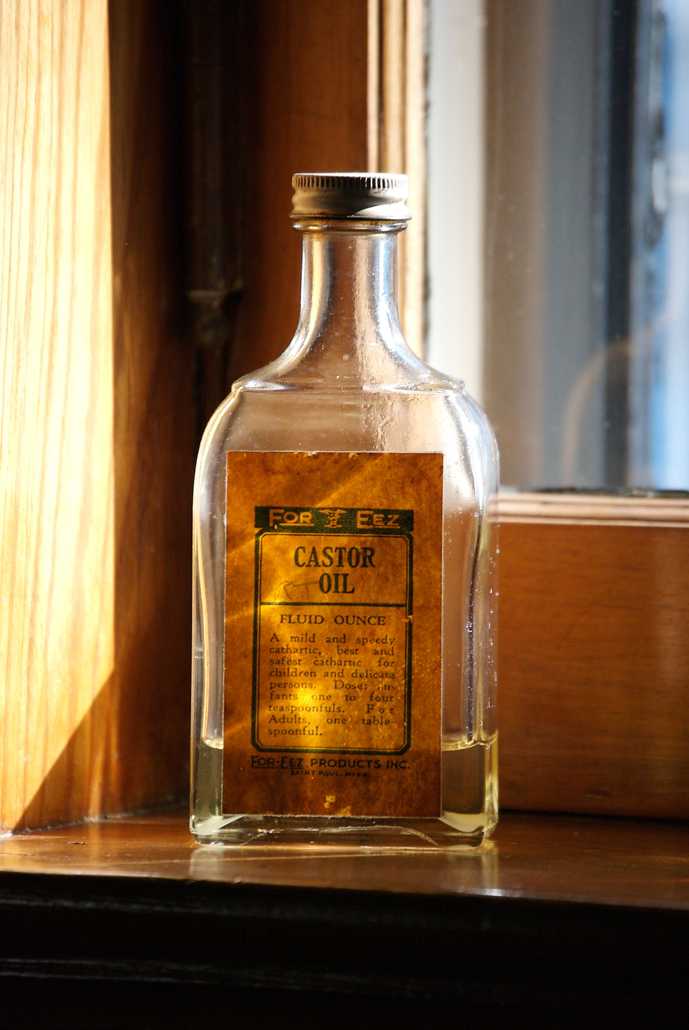 Old-fashioned bottle of castor oil in sunny windowsill.