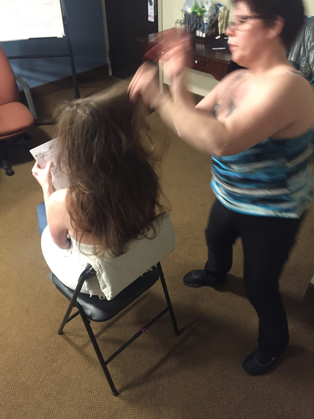 The therapist applies a series of brisk massage movements to the client's scalp.  Client is seated in a chair.