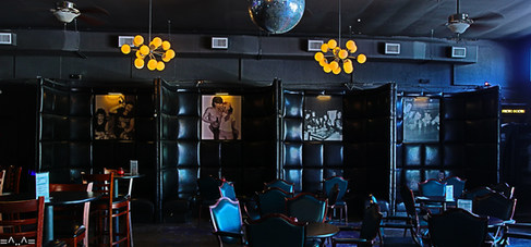 Tall black leather booths circle around tables for a comfy, cozy, private setting.