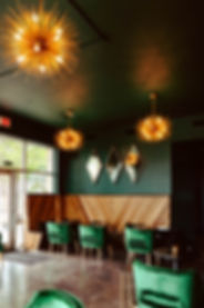 Velouria's deep green interior is lit wit funky chandeliers and rich wood.