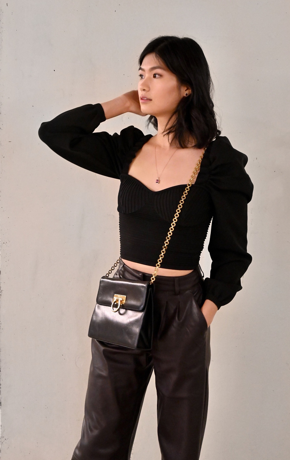 Dark brown leather pants styled with a cropped, bustier style puff sleeve knit sweater with a sweetheart neckline. Paired with a Salvatore Ferragamo Gancini purse