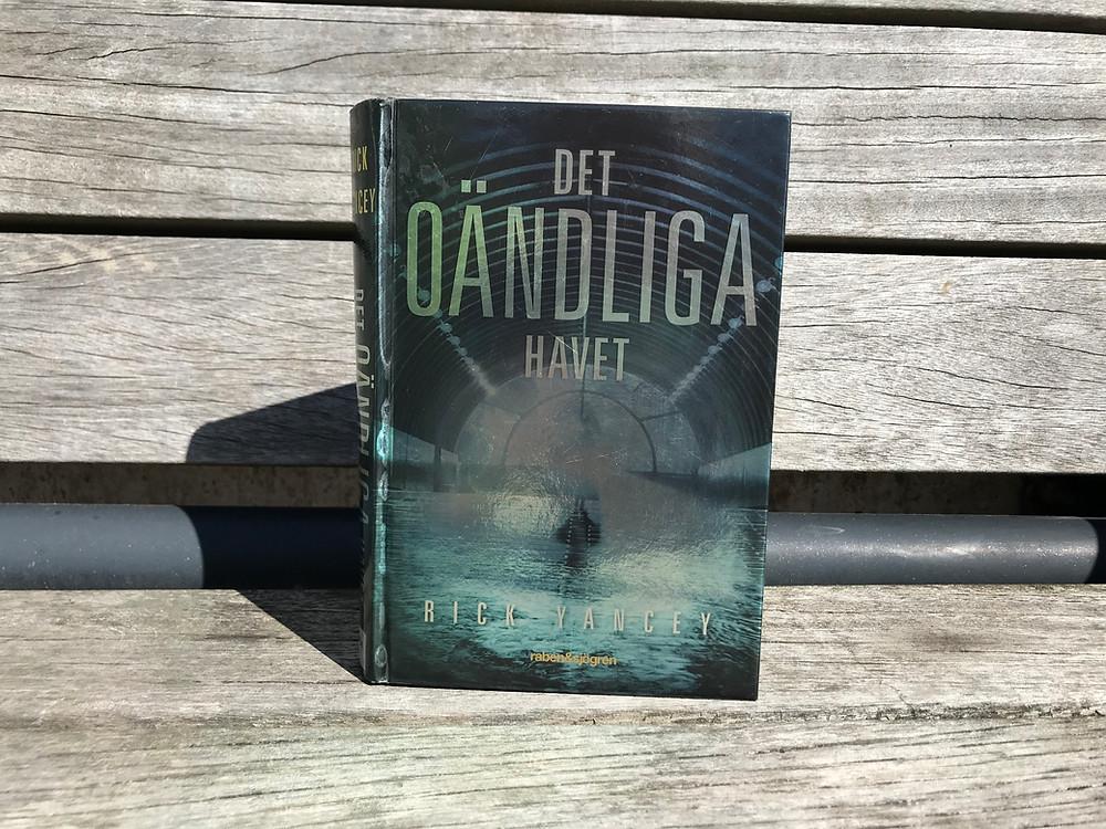 Boken Det oändliga havet står på en grå och väderbiten träbänk
