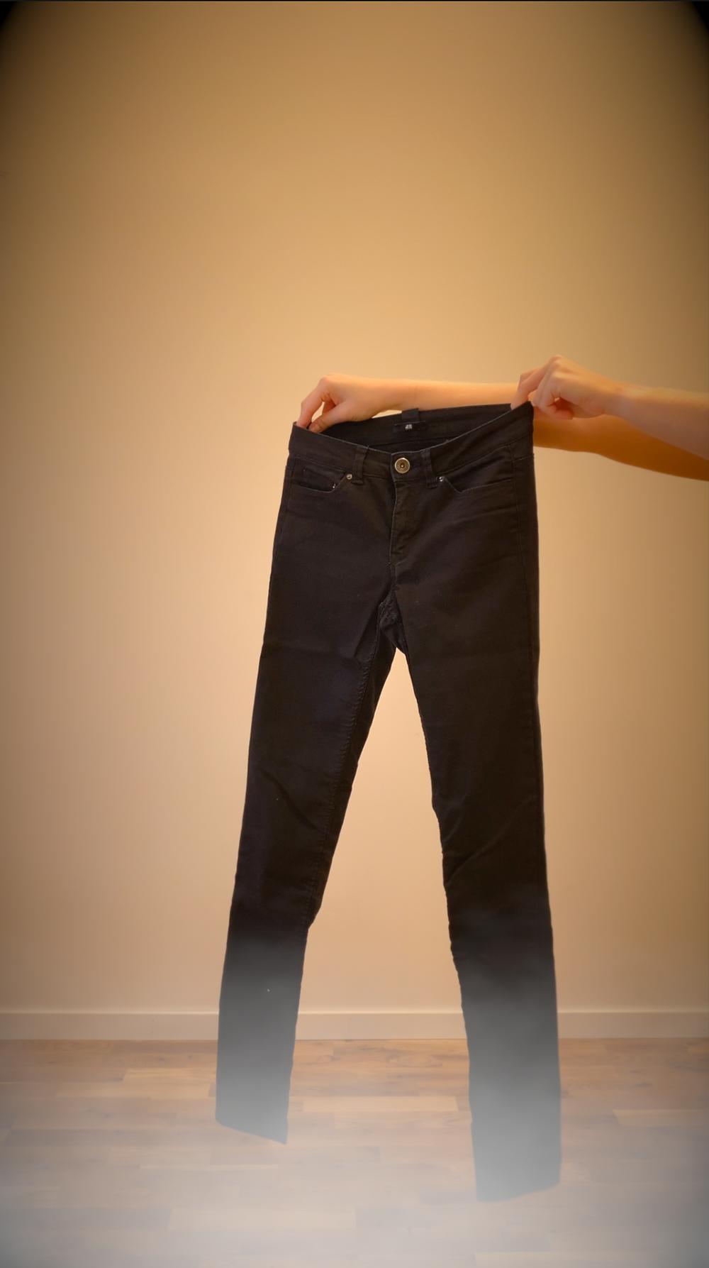 Ett par svarta jeans som hålls upp av ett par händer.
