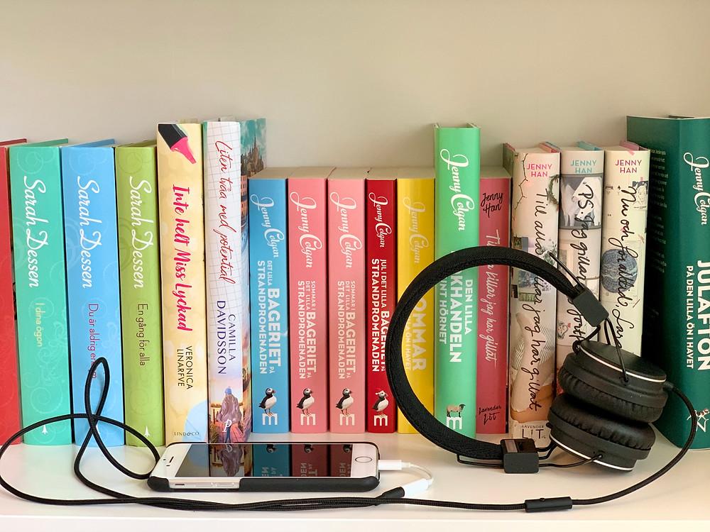 En telefon och ett par hörlurar ligger på kanten på en bokhylla som är full med färgglada böcker.