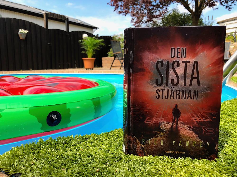 I förgrunden står boken Den sista stjärnan. I bakgrunden syns en pool med en luftmadrass i, i form av en skiva vattenmelon