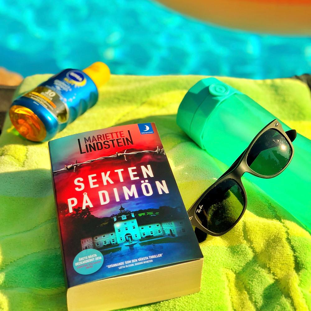 På en grön handduk intill en pool ligger boken Sekten på Dimön. Bredvid boken ligger en grön vattenflaska från Hidrate Spark, ett par Ray Ban solglasögon och en solkräm