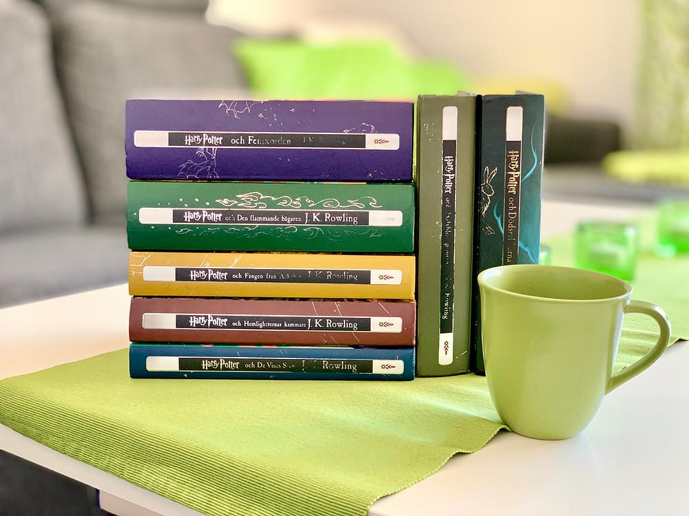 Alla Harry Potter böckerna ligger i en hög på ett bord. Två av böckerna står lutade möt de andra böckerna. Framför bokhögen står en grön kaffemug.