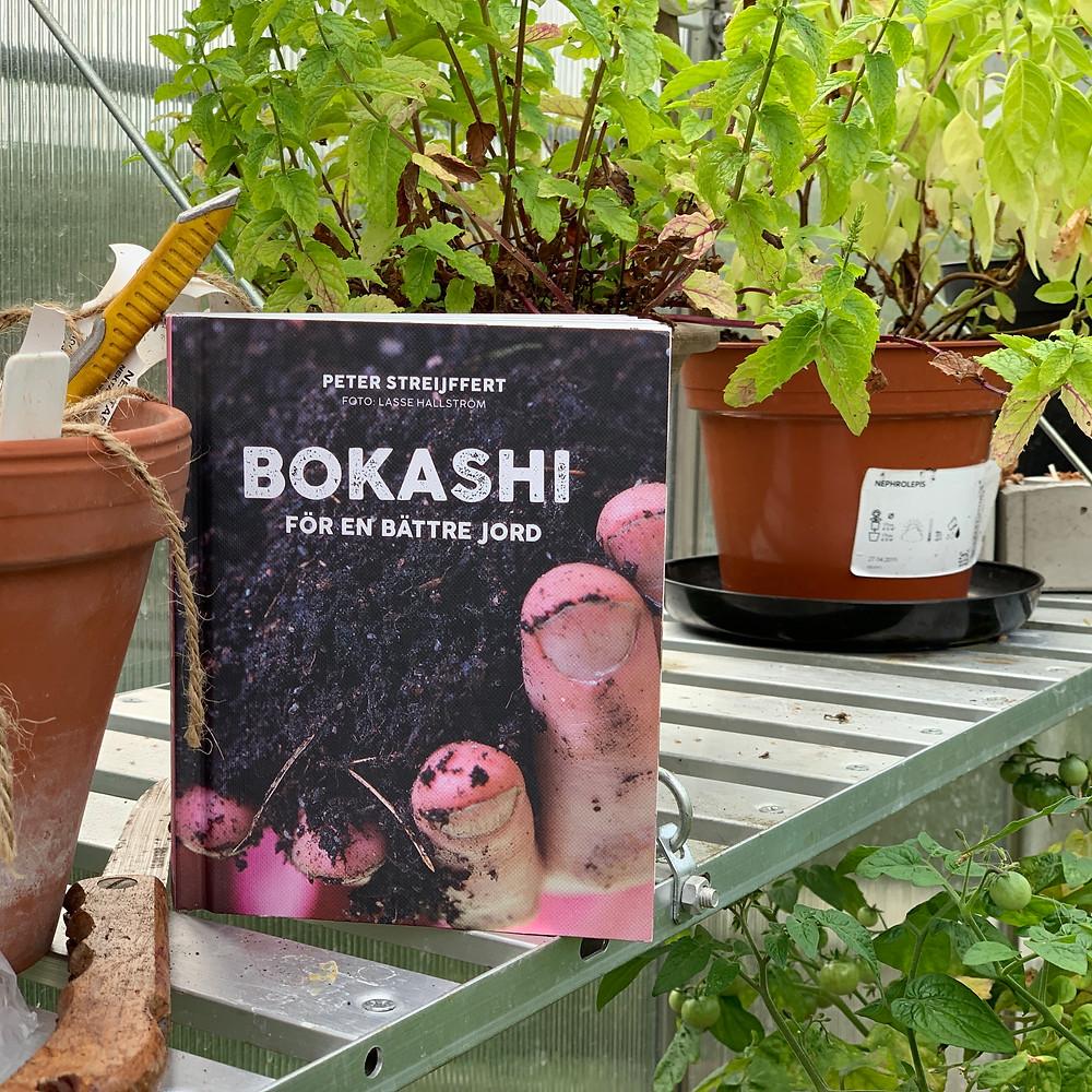 Boken Bokashi: En bättre jord står på en hylla i ett växthus med några växter i bakgrunden
