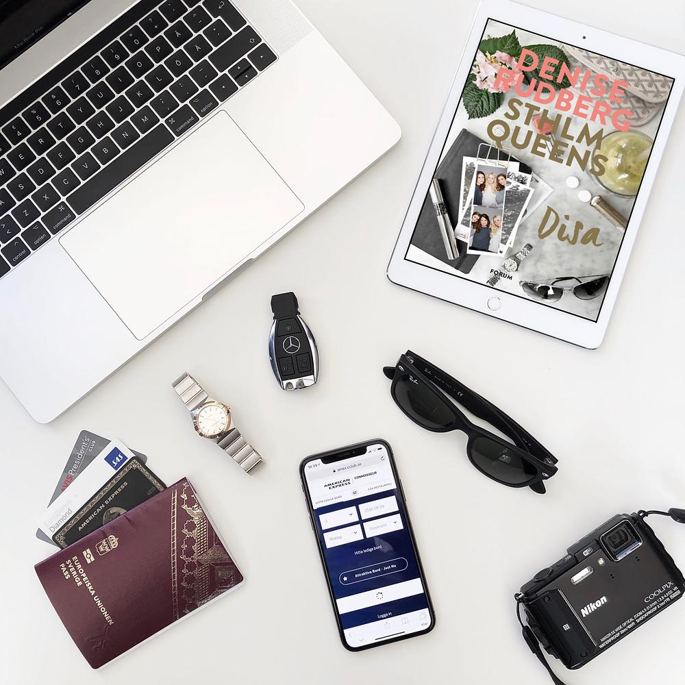 En vit ipad ligger på ett vitt bord med omslaget till boken Disa synlig på skärmen. Runt omkring ligger en öppen Macbook Pro, ett par Ray Ban glasögon, en bilnyckel till en Mercedes, en Omega klocka, en Nikon kamera, en iphone X, ett pass och några betal- och medlemskort.
