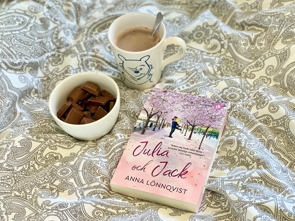 En bok, en skål med chokladbitar och en mugg med varmchoklad ligger på en säng.