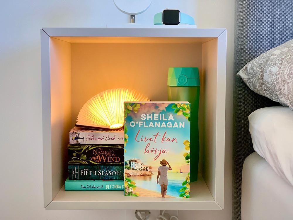 En bokhög ligger i ett ihåligt sängbord. Framför bokhögen står boken Livet kan börja.