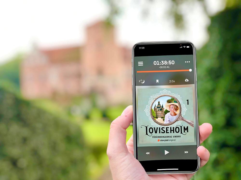 En hand håller upp en telefon där ljudboken Loviseholm syns på skärmen. i bakgrunden ligger ett vackert slott omringad av grön natur.