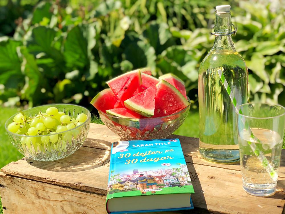 I förgrunden ser vi en trälåda som används som picknickbord. På lådan står glasskålar, med vindruvor och vattenmelon, en glasflaska med saft i, ett glas saft med ett grön randigt sugrör och boken 30 dejter på 30 dagar. I bakgrunden syns grön natur