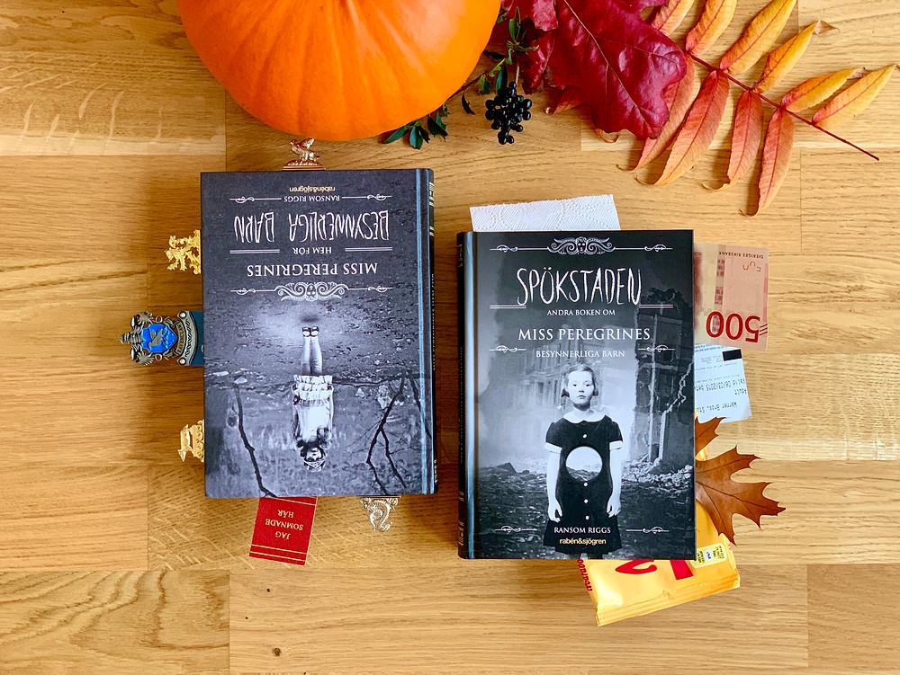 Två böcker ligger bredvid varandra. Den ena är full med bokmärken, den andra är full med udda saker som papperslappar, sedlar och biljetter. Bredvid böckerna är det dekorerat med en pumpa och lov i höstens färger.
