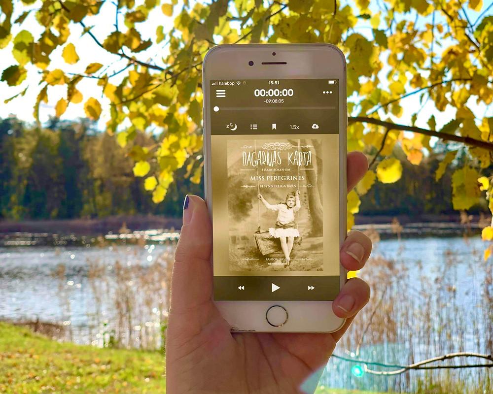 En hand håller upp en telefon med ljudboken Dagarnas karta synlig på skärmen. I bakgrunden syns ett träd med gula löv och en sjö.