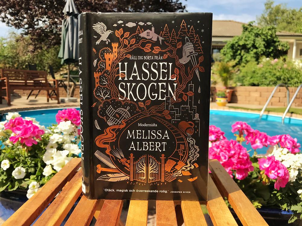 I förgrunden syns Melissa Alberts bok Hasselskogen, originaltitel The Hazelwood. I bakgrunden syns en pool, en frodig grön trädgård och krukor med rosa och vita blommor