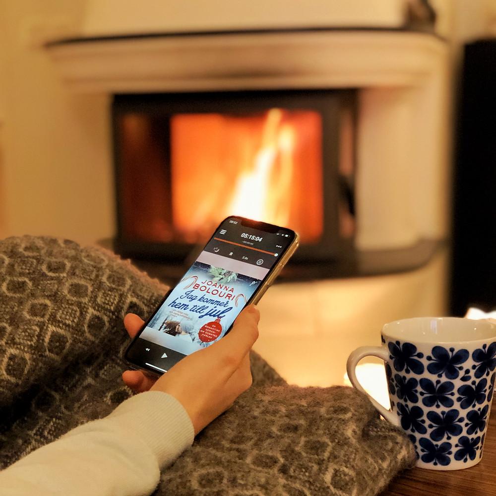 """En hand som håller i en iPhone, på skärmen syns ljudboken: """"Jag kommer hem till jul"""". Personen sitter under en filt med en kaffekopp bredvid sig och en brasa syns i bakgrunden."""