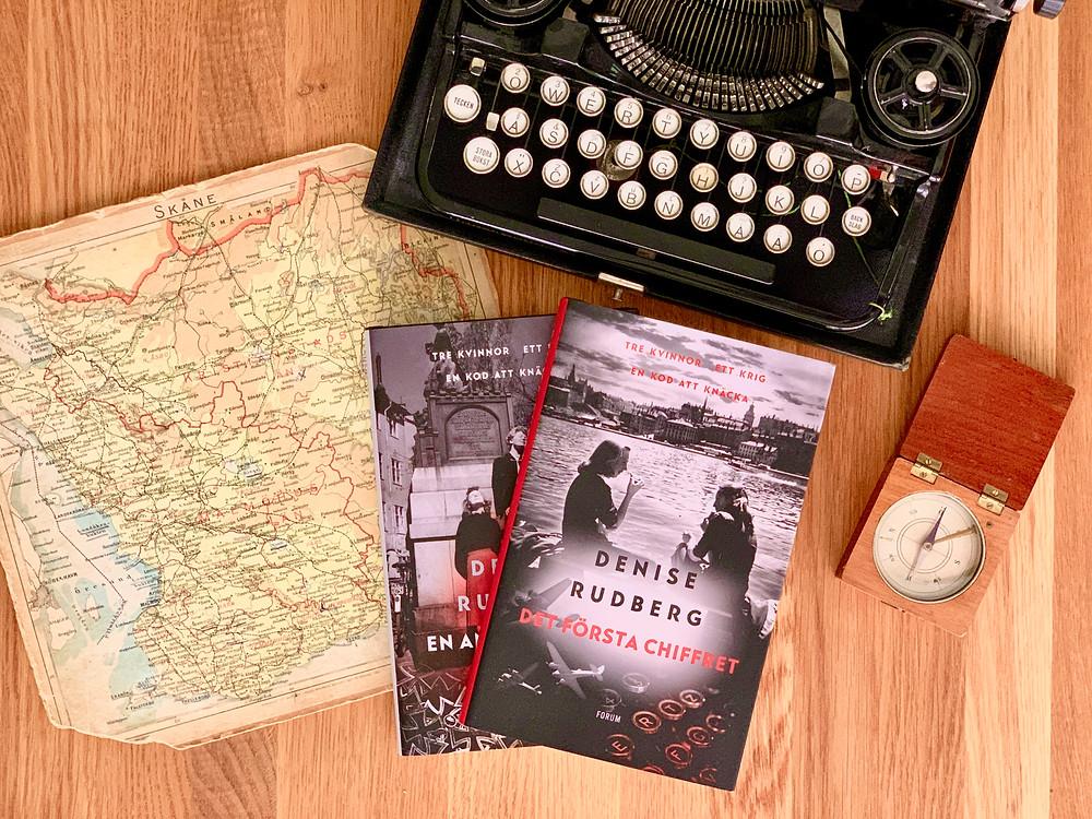 Två böcker ligger i mitten av bilden. Runt omkring står en skrivmaskin, en gammal kart och en gammal kompass