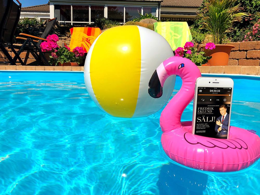På bilden syns en rosa, uppblåsbar badleksak i formen av en flamingo, i den står en vit iphone med ljudboken Sälj synlig på skärmen, allt ihop flyter runt i en pool. I bakgrunden syns en badboll som också flyter runt i vattnet, solstolar och blommor.