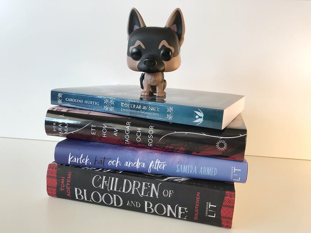 En bokhög bestående av följande böcker: Children av blood and bone, Kärlek, hat och andra filter, Ett hov av taggar och rosor, och Döttrar av natt. Ovanpå bokhögen sitter en funko pop figur föreställande en Schäfer hund