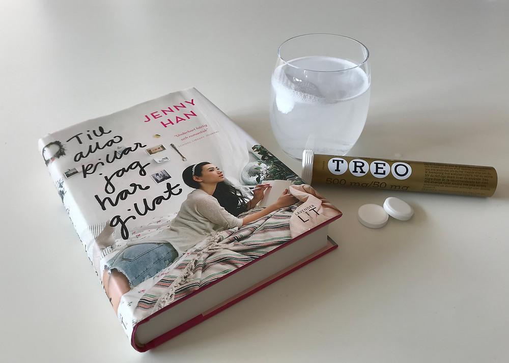 Boken Till alla killar jag har gillat, ligger på ett vitt bord. Bredvid boken står ett vattenglas med en brustablett i, en packet med Treo huvudvärkstabletter och två lösa brustabletter