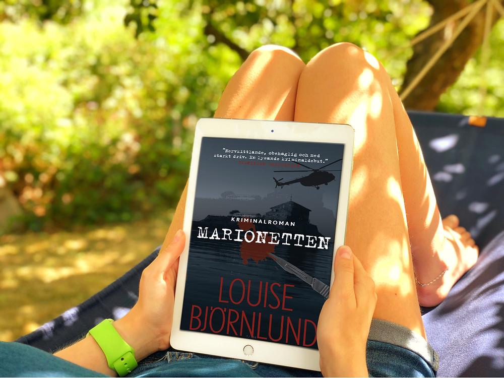 På bilden syns benen på en person som ligger i en hängmatta. I handen har personen en vit ipad där omslaget till boken Marionetten visas. I bakgrunden syns gröna buskar och träd.