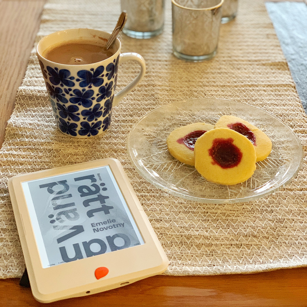 En Storytel reader ligger på ett bord. Bredvid står en mugg med varmcholkad och ett fat med hallongrottor.