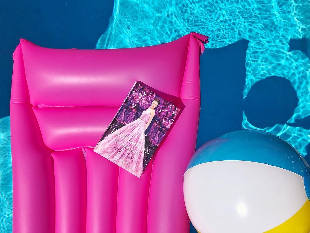 På bilden syns en neon rosa luftmadrass som flyter runt i en pool. På luftmadrassen ligger boken Drottningen och bredvid flyter en randig badboll