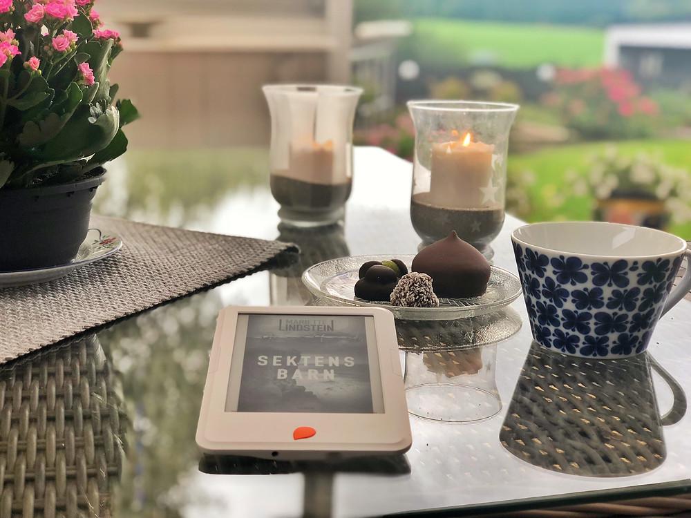 En Storytel Reader ligger mitt på ett bord med bokomslaget till Sektens barn synligt på skärmen. Bredvid den finns en kaffekopp och i bakgrunden syns en assiett med småkakor, två ljusstakar, en blomma och en duk. Bilden är tagen på en uteplats under tak, med naturen synlig i fjärran.
