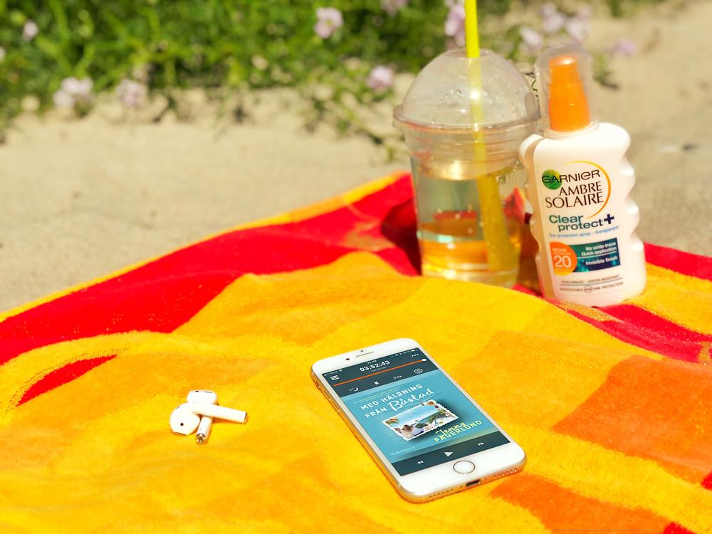 En vit iphone med ljudboken Med hälsning från Båstad synligt på skärmen. Iphonen ligger på en orange strandhandduk med ett par Apple airpods hörlurar bredvid sig och i bakgrunden syns en solkräm och en ta med mugg med iste. Runt omkring syns stranden.