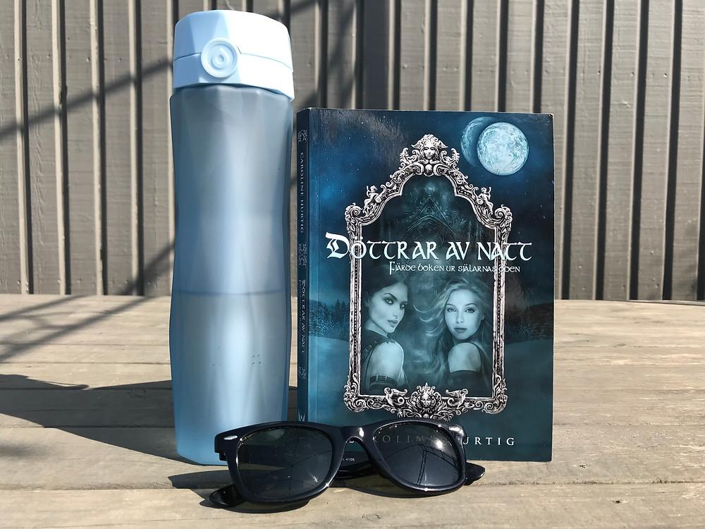 Boken Döttrar av natt står uppställd på ett trädäck med en ljusblå vattenflaska bredvid och ett par svarta solglasögon framför