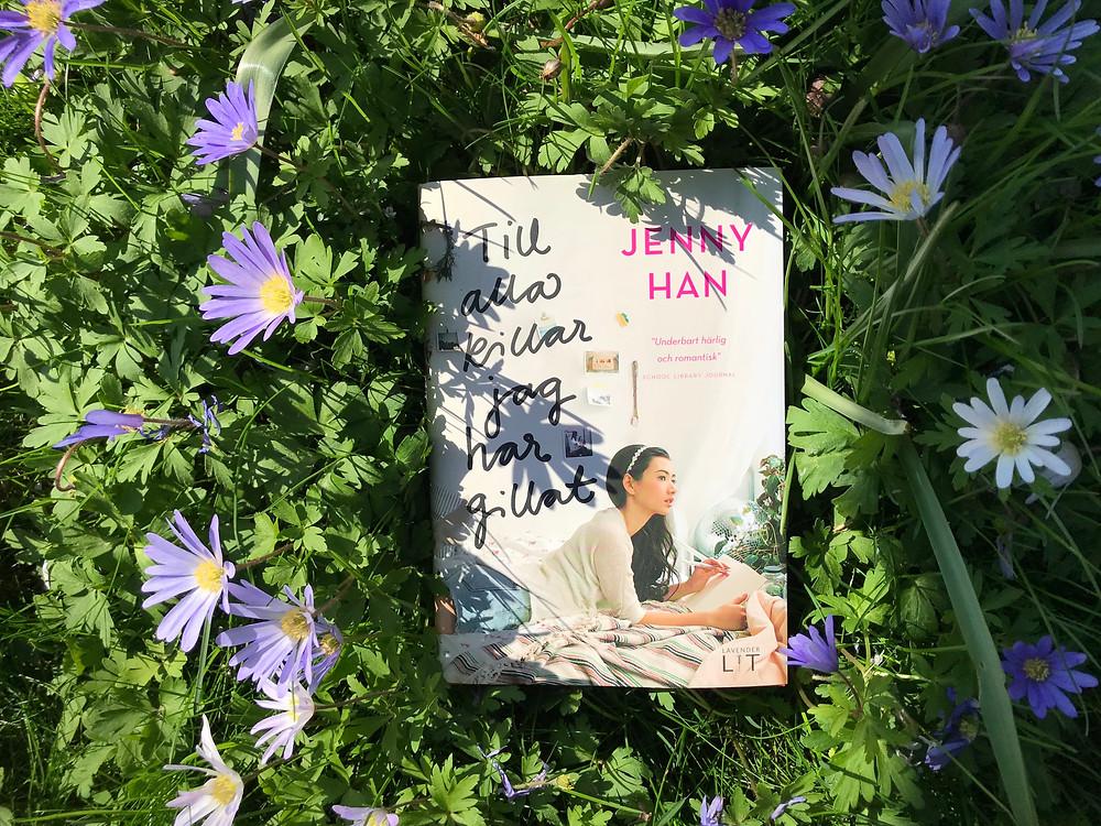 Boken Till alla killar jag har gillat, ligger mitt i en gräsmatta full med lila blommor