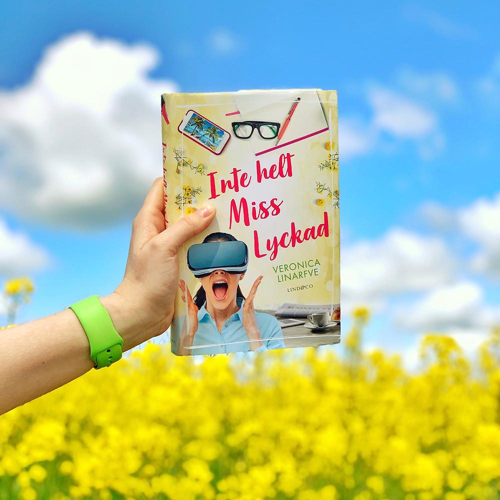 """En hand som håller upp boken """"Inte helt Miss Lyckad"""" framför ett gult rapsfält och en blå himmel."""