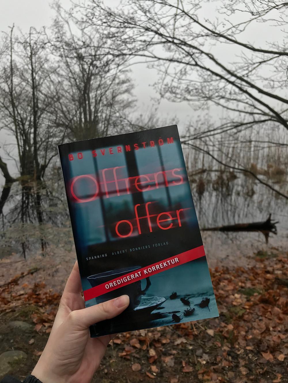 En hand som håller i boken Offrens offer, med en några nakna träd och en sjö i bakgrunden. En tjock dimma ligger över allt ihop och gör att naturen ser mystisk ut