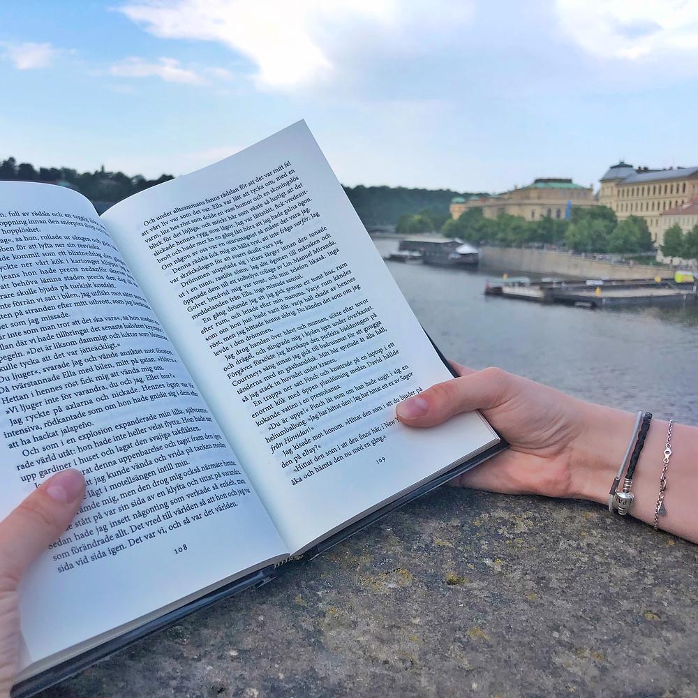 Ett par händer som håller i en bok med stöd mot kanten på en stenmur. I bakgrunden syns hav och kanten på en stad.