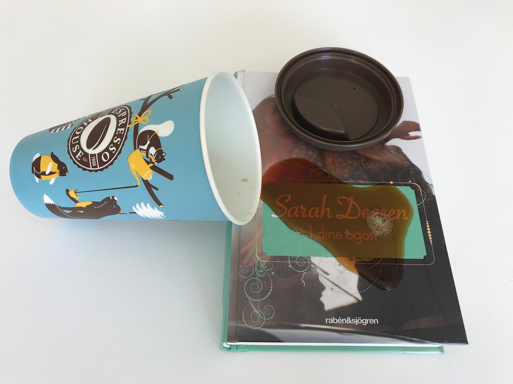 På ett vitt bord ligger boken I dina ögon. En ta med mugg har vält och spillt ut kaffe över bokens framsida
