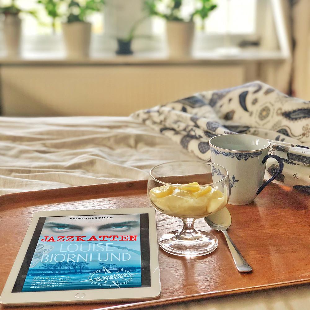 """På en säng står en bricka med en kaffekopp, en efterrätt och en iPad. På ipaden syns omslaget till boken: """"Jazzkatten"""". I bakgrunden ser man en fönsterkarm med blommor."""