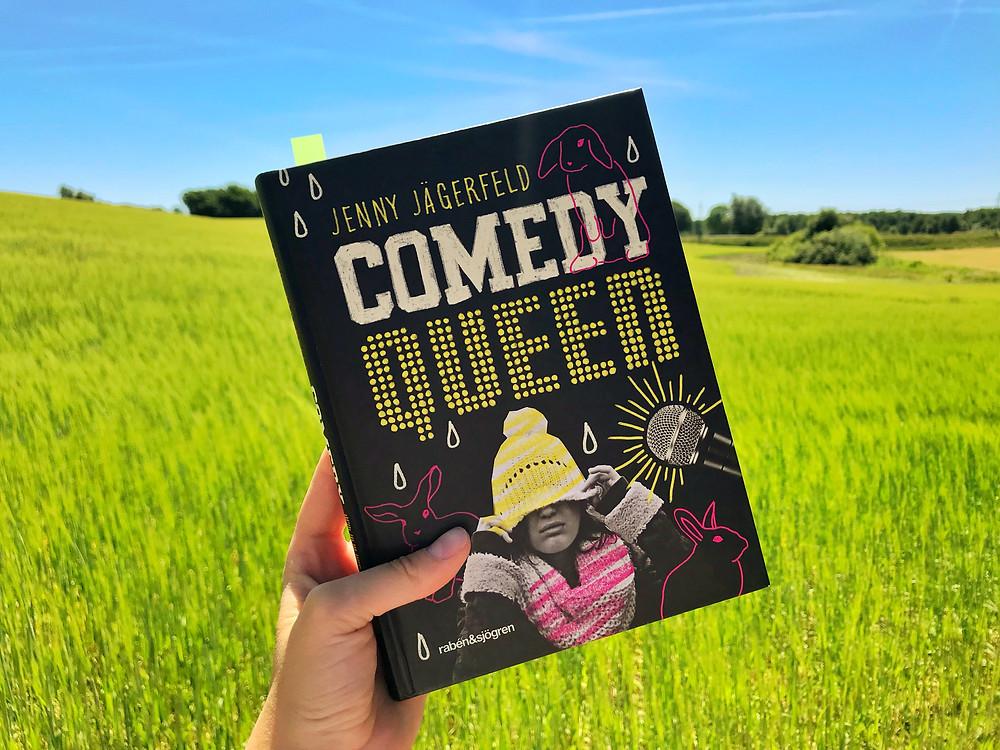 På bilden syns en hand som håller i boken Comedy Queen. I bakgrunden syns en ljusgrön åker och en klarblå himmel