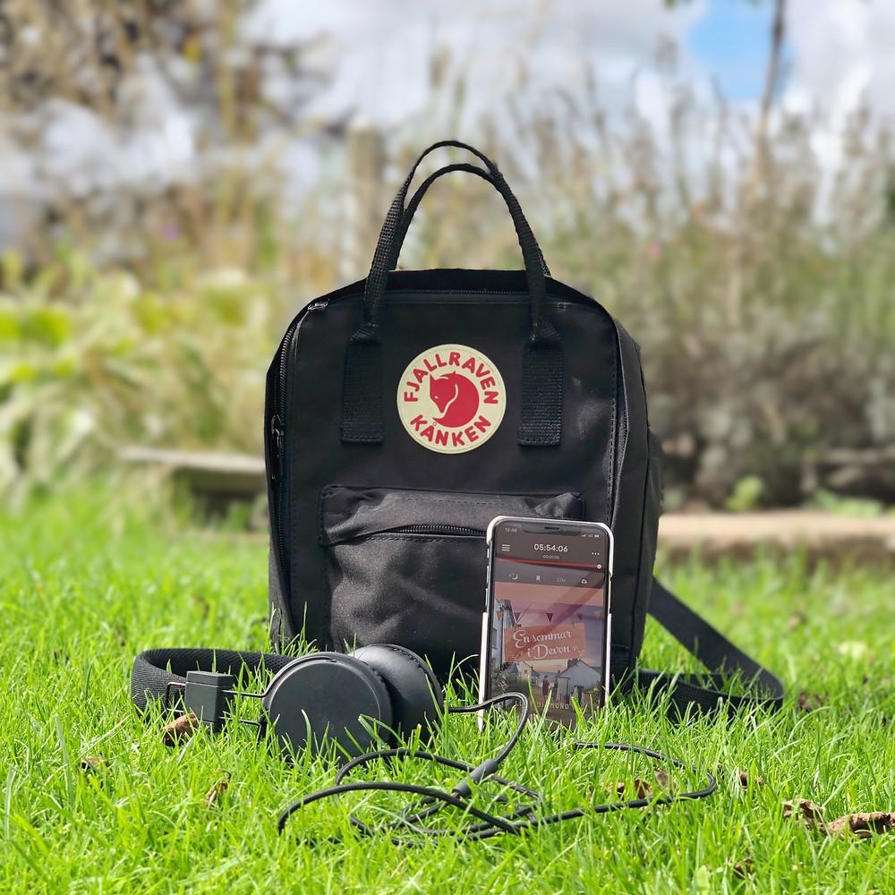 En telefon står på en gräsmatta lutad mot en ryggsäck med ett par hörlurar liggandes bredvid.