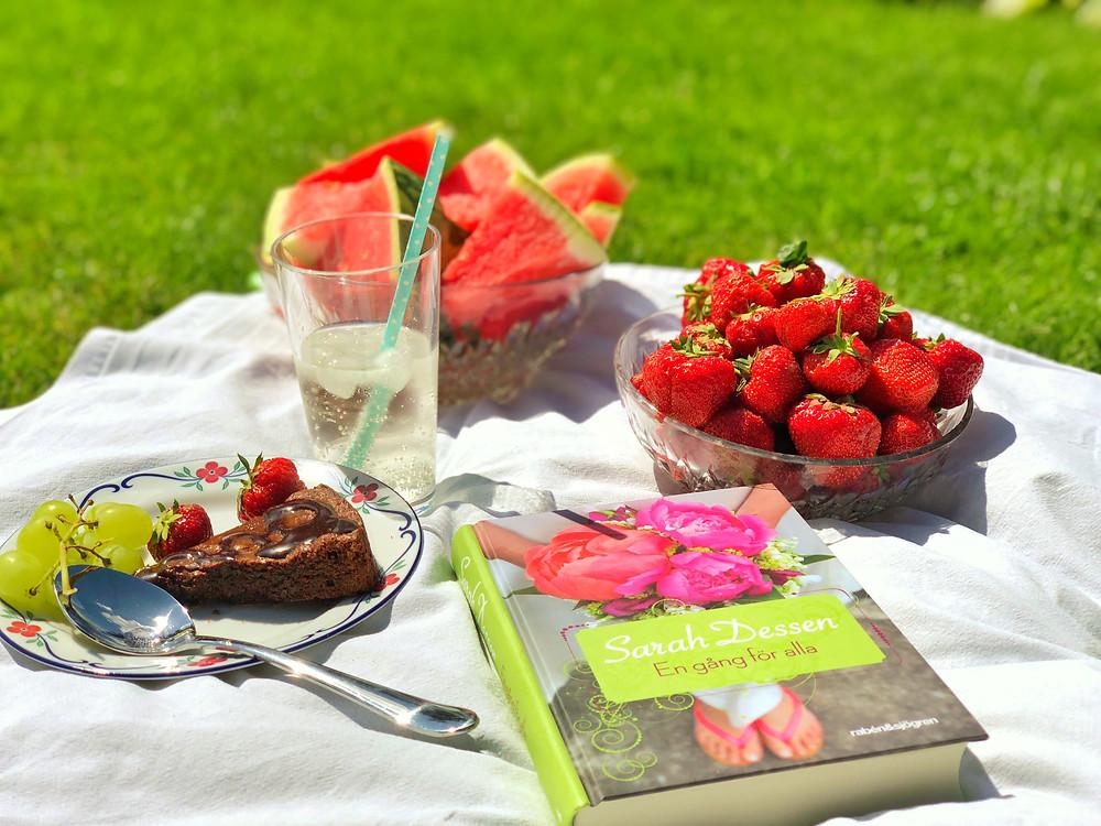Bilden visar en picknick. Främst i bild ligger boken En gång för alla och runt boken finns en glasskål med jordgubbar, en glasskål med vattenmelon, en tallrik med kladdkaka och ett glas med saft. Alltihop ligger på ett vitt lakan och i bakgrunden ser man grönt gräs